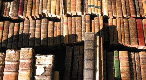 Several volumes of dusty, old books on a shelf.