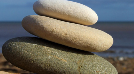 Three, smooth stones stacked on top of each other and sitting on the beach or the shore of a sea.