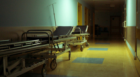 Three gurneys in an empty hospital hallway.