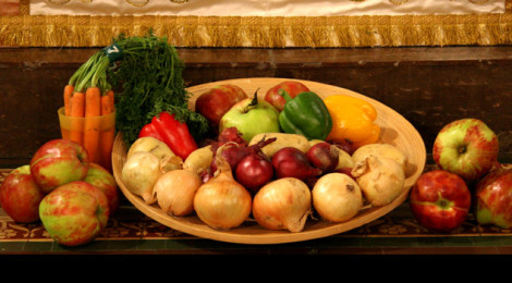A basket of colorful vegetables sitting on table in between two piles of apples and carrots.