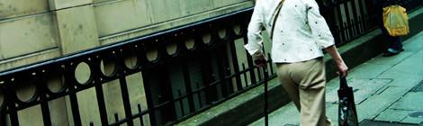 A woman using a cane walks down a city sidewalk.