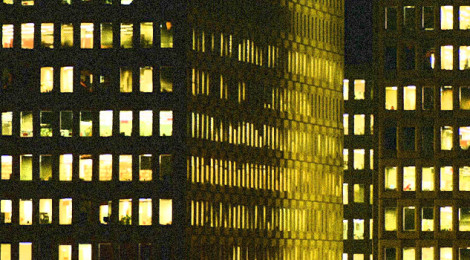 Close-up image of two city buildings at night, with lights on inside and illuminating the windows.