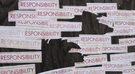 "Multiple bumper stickers with the word ""Responsibility"" attached to a wall."