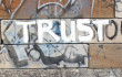 "A wall on an outside building covered with graffiti that is nondescript, except for the word ""Trust."" FreeImages.com/Berkeley Robinson"