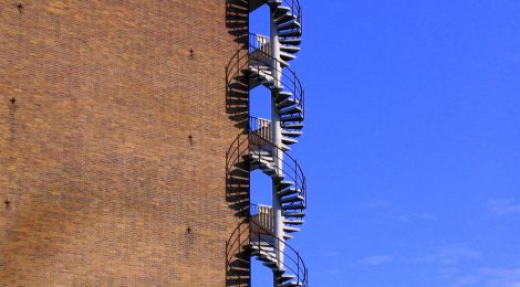 An ascending staircase, on the outside of a building, that resembles the DNA double helix. PHOTO © Artyom Korotkov/FreeImages.com