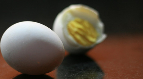 Close-up image of two hard-boiled eggs, one half eaten.