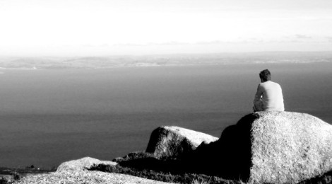 A man sitting alone atop a rock, overlooking a vast sea.