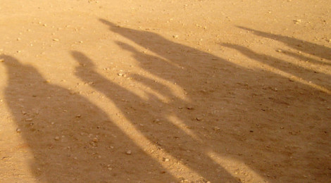 Shadows of a group of people cast onto a desert floor on a sunny day.