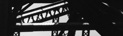 A primarily black-and-white photograph of the supports under a bridge, with areas of blue sky showing through.