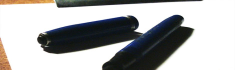 Close-up image of a fountain pen laying on a blank piece of paper on a clipboard.