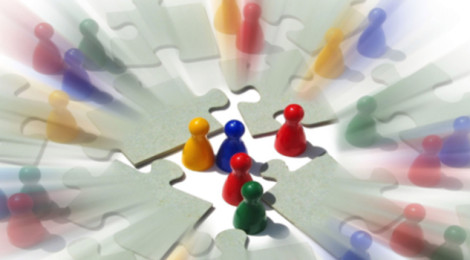 Multicolored board game player pawns are assembled like groups of people in conversation amid disconnected puzzle pieces.