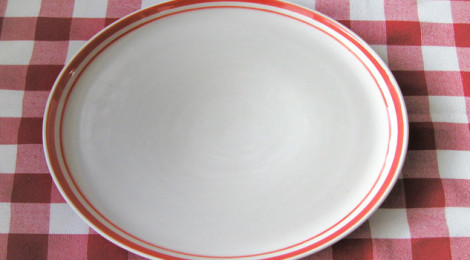 An empty plate on a table covered with a checkered tablecloth.