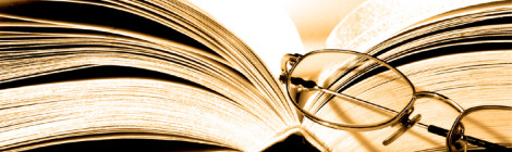 A pair of reading glasses sits atop an open book.